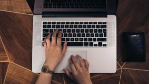 mujer escribiendo portátil
