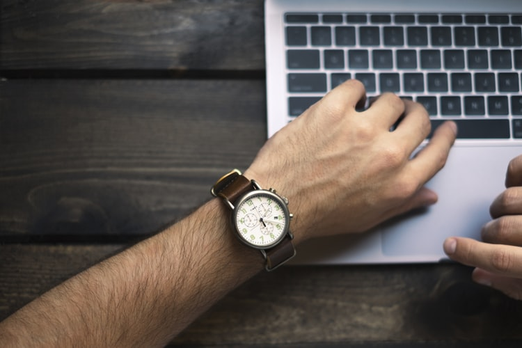 Mano sobre teclado con reloj en la muñeca
